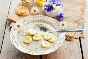 Healthy breakfast: porridge with bananas. Traditional dish  banana  bouquet  bowl  breakfast  cake  cereal  chamomile  cookbook  cooked  cornflower  cuisine  diet  dieting  eating  flakes  food  fresh  gourmet  grain  granola  healthy  heap  honey  ingredient  kitchen  light  lunch  meal  morning  muesli  napkin  natural  nutrition  oat  oatmeal  organic  plate  porridge  portion  recipe  soup  spoon  table  taste  tasty  traditional  vegetarian  vintage  vitamin  wooden